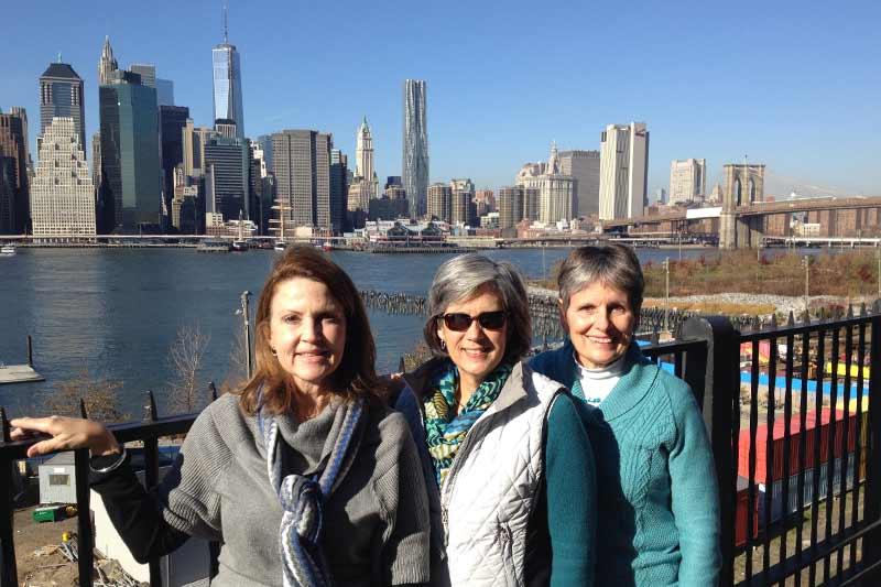 three women in front of new york city skyline