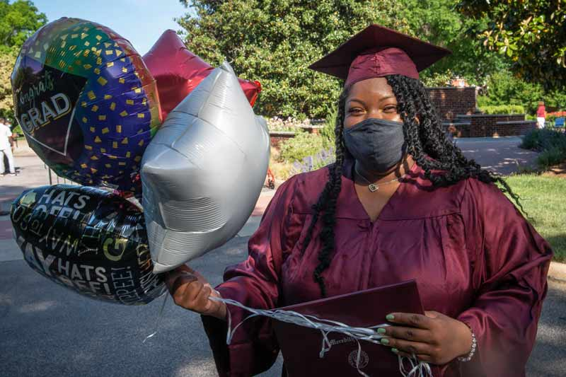 Student with her diploma and balloons