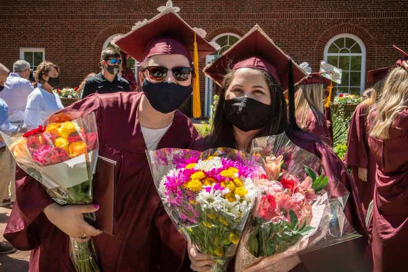 Students with flower bouquets after graduation
