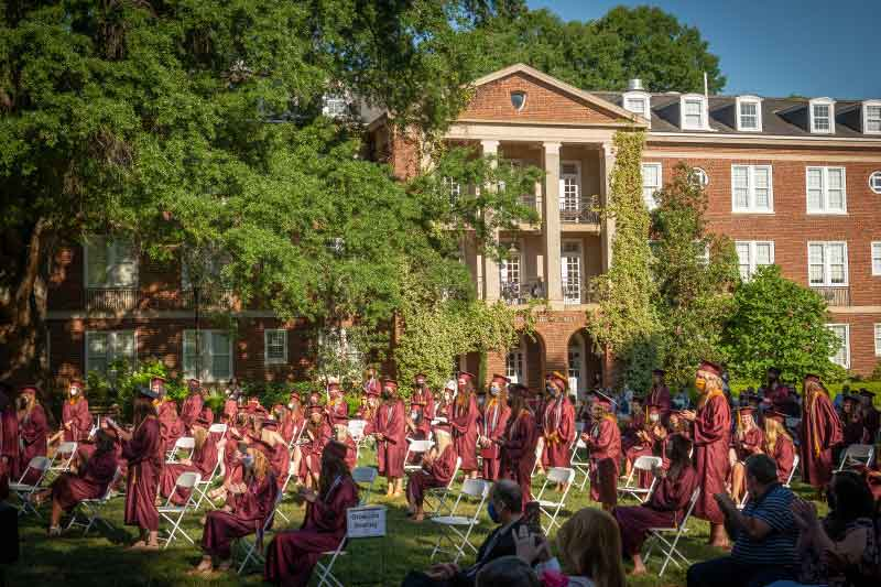 Students at graduation behind Johnson hall
