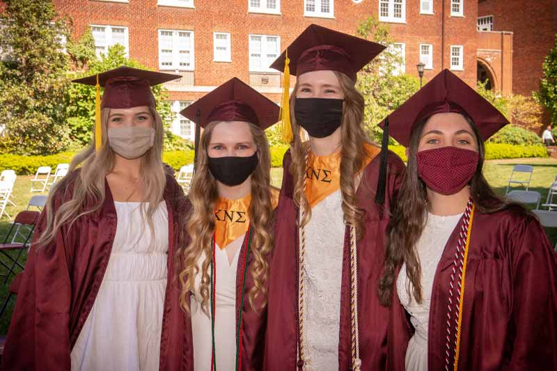 Four students smiling at camera with masks on
