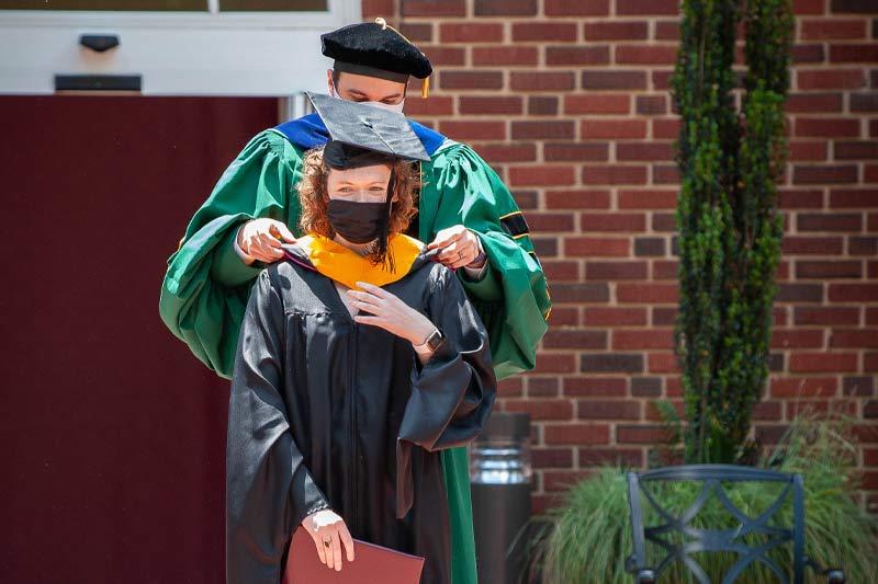 A new graduate receiving their hood