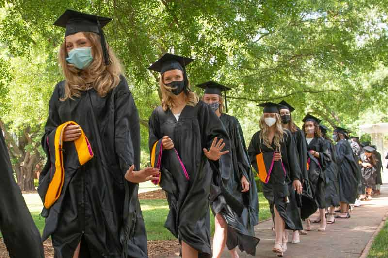New graduates walking to receive their diploma with hood in hand