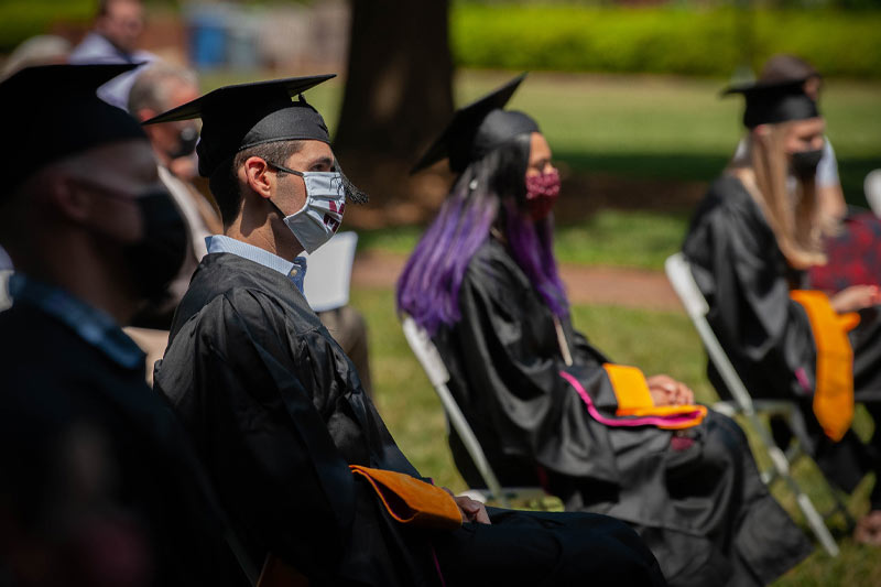 New graduates watching a speaker at hooding ceremony