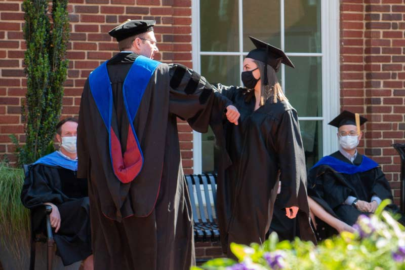 Transferring of degrees with new graduate and professor elbow bumping to celebrate
