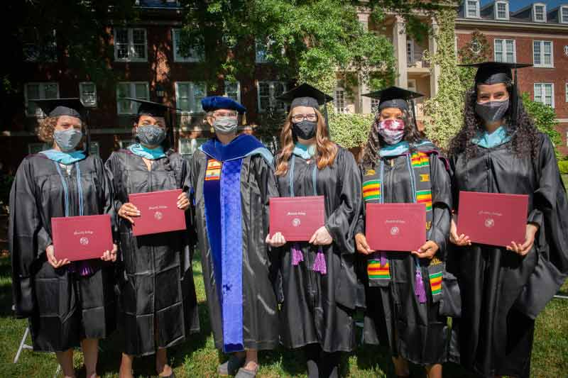 New graduates pose with their degrees and hoods