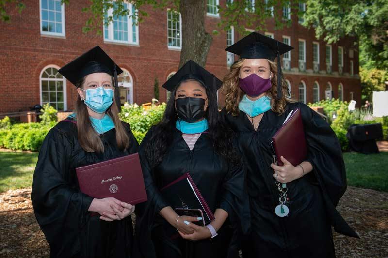 New graduates posing with diplomas and hoods