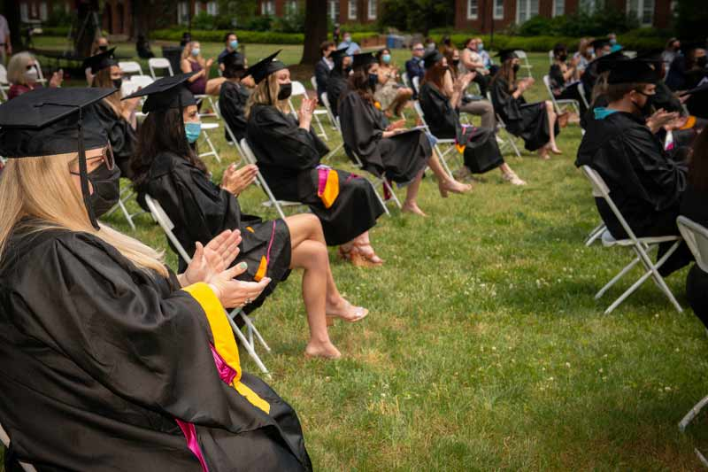 new graduates clapping at hooding ceremony